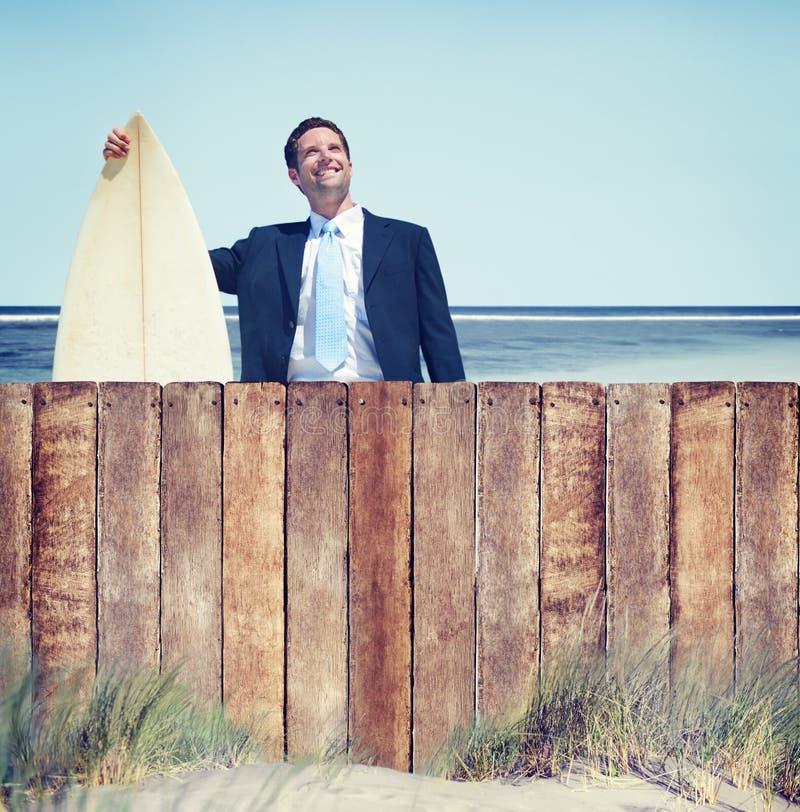 Affärsman med surfingbrädan vid stranden royaltyfria bilder
