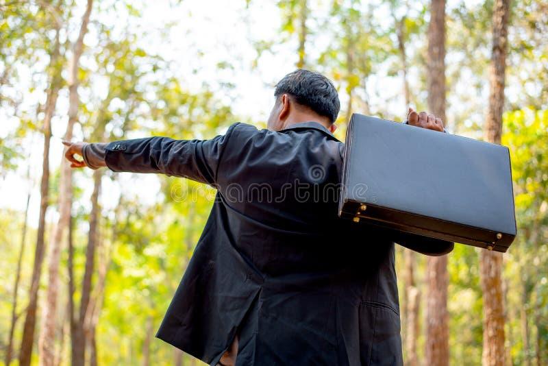 Affärsman med svart dräkt- och portföljblick till skogen och punkt till några riktningar som också tänker om plan av land eller fotografering för bildbyråer