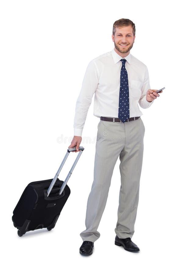 Affärsman med telefonen och resväskan som ser kameran arkivbilder