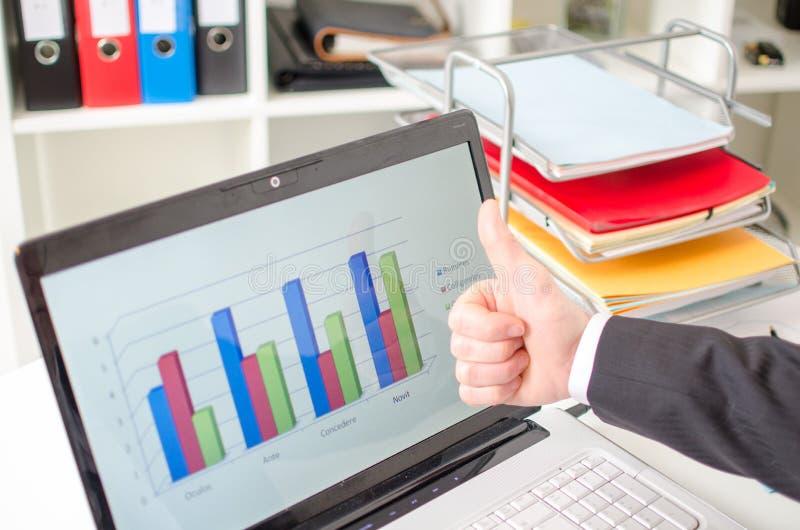 Affärsman med tummar upp framme av en graf arkivfoto