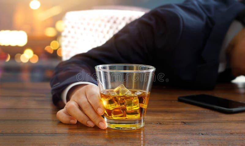 Affärsman med whiskybourbonexponeringsglas, druckit sova royaltyfri bild