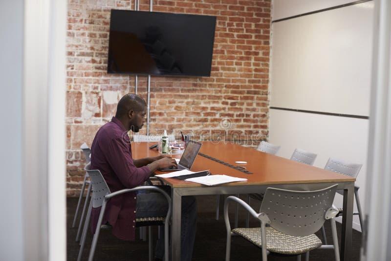 Affärsman In Meeting Room som arbetar på bärbara datorn royaltyfri bild