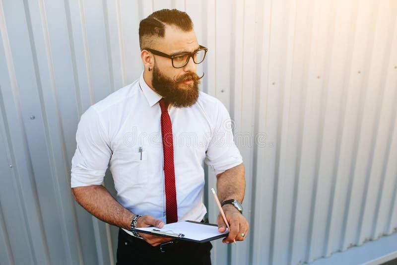 Affärsman mot en vit vägg arkivbild