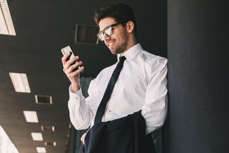 Affärsman nära affärsmitt genom att använda mobiltelefonen arkivfoton
