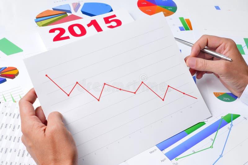 Affärsman observera ett diagram med en nedåtriktad trend royaltyfri bild