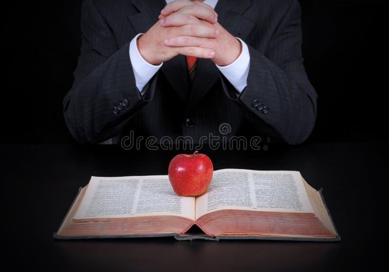 Affärsman och äpple på boken royaltyfria foton