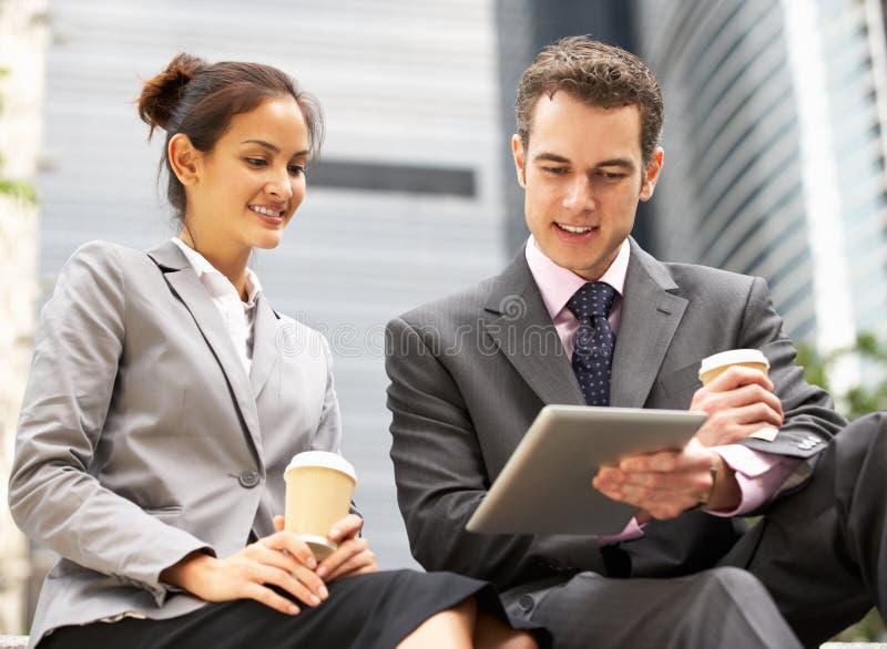 Affärsman och affärskvinna genom att använda den Digital tableten arkivfoto