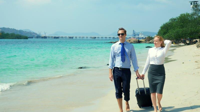 Affärsman och affärskvinna med en resväska som promenerar den vita sandstranden på ön arkivfoto