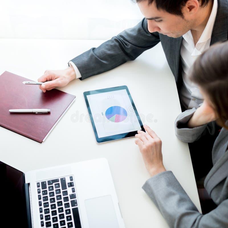 Affärsman och affärskvinna som analyserar en statistisk affär royaltyfria foton