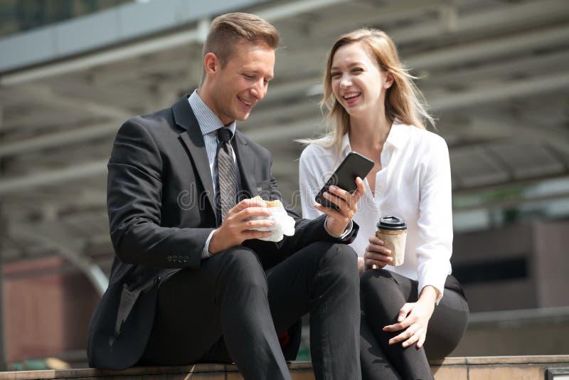 Affärsman och affärskvinna som använder smartphonen som äter frukosten och tillsammans dricker kaffe i stad utomhus Spännande kol arkivfoton