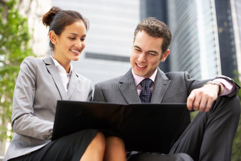 Affärsman och affärskvinna som diskuterar förlagan arkivbild