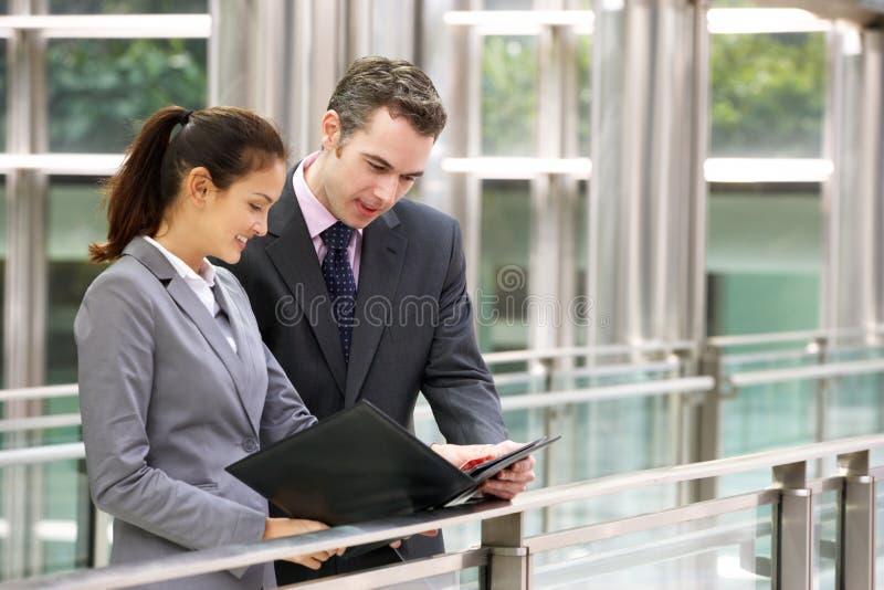 Affärsman och affärskvinna som diskuterar förlagan arkivfoto