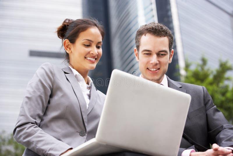 Affärsman och affärskvinna som fungerar på bärbar dator royaltyfria foton