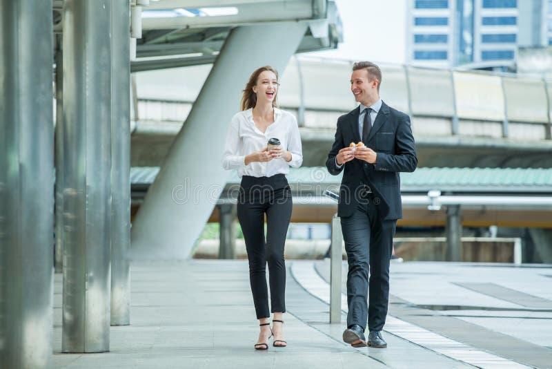 Affärsman och affärskvinna som går och talar på gatan i stad utanför kontor med, unga par som diskuterar och äter royaltyfri fotografi