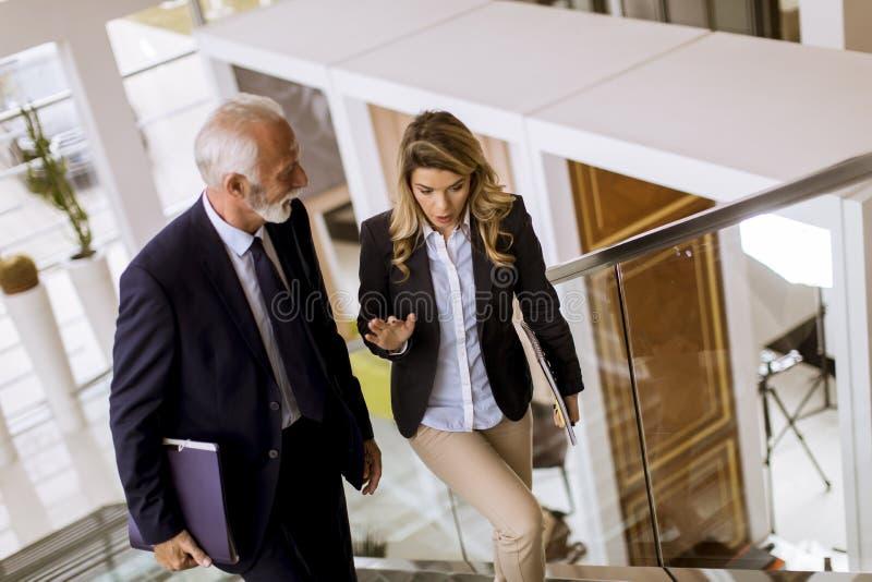 Affärsman och affärskvinna som går och tar trappa i av royaltyfri fotografi