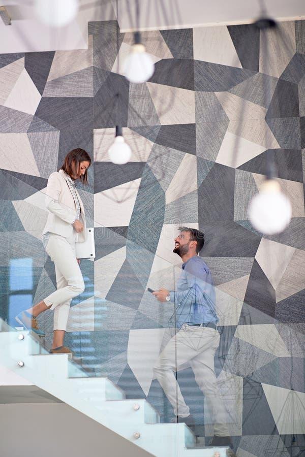 Affärsman och affärskvinna som går upp trappan arkivbilder