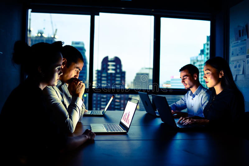 Affärsman och affärskvinna som på övertid arbetar med datoren på natten royaltyfria bilder