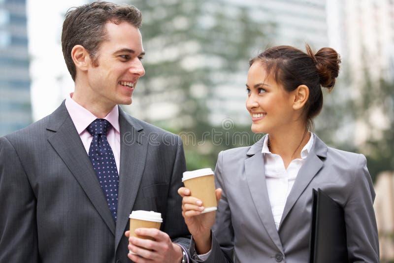 Affärsman och affärskvinna som pratar i gata arkivbild