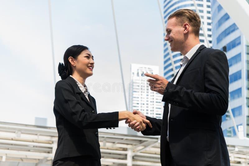 Affärsman och affärskvinna som skakar händer för demonstrering av deras överenskommelse att underteckna överenskommelse eller avt royaltyfria bilder