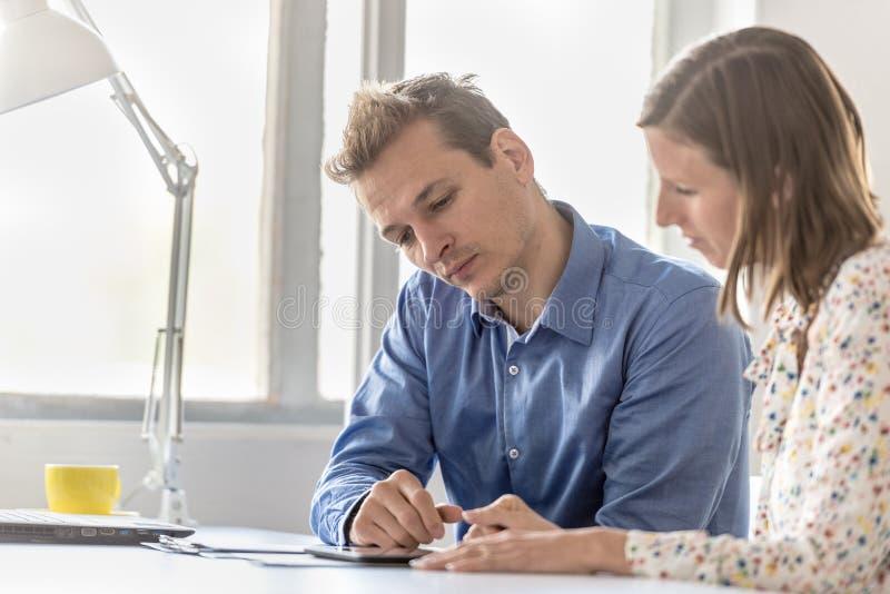 Affärsman och affärskvinna som tillsammans arbetar arkivfoto