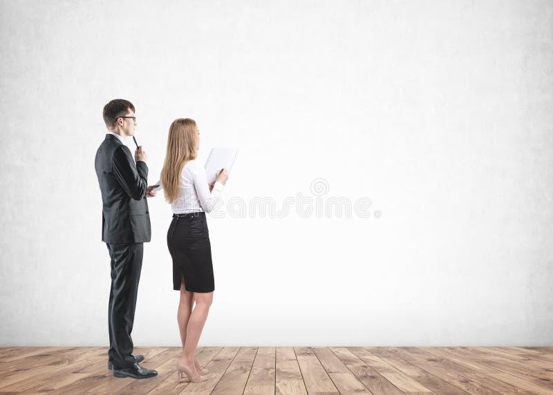 Affärsman- och affärskvinnablick på den tomma väggen arkivfoton