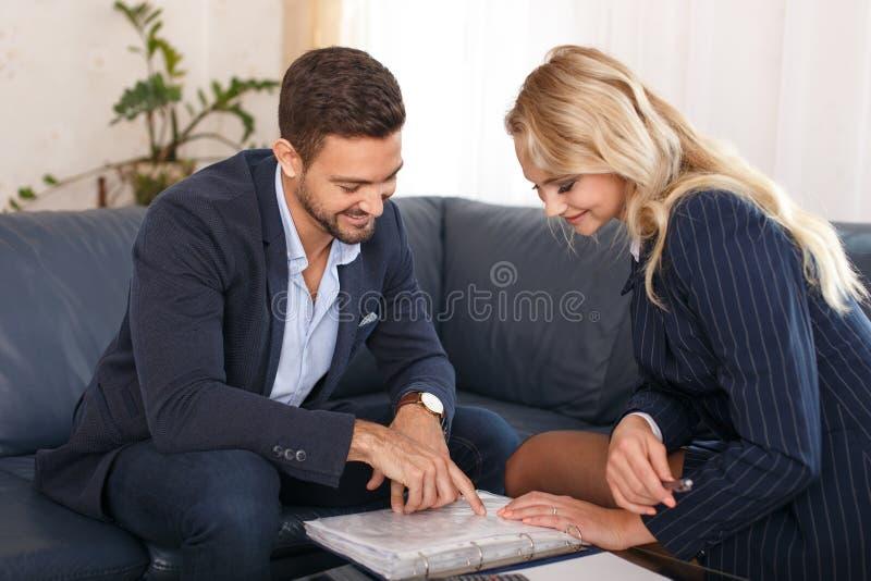 Affärsman- och affärskvinnagranskningavtal arkivfoto