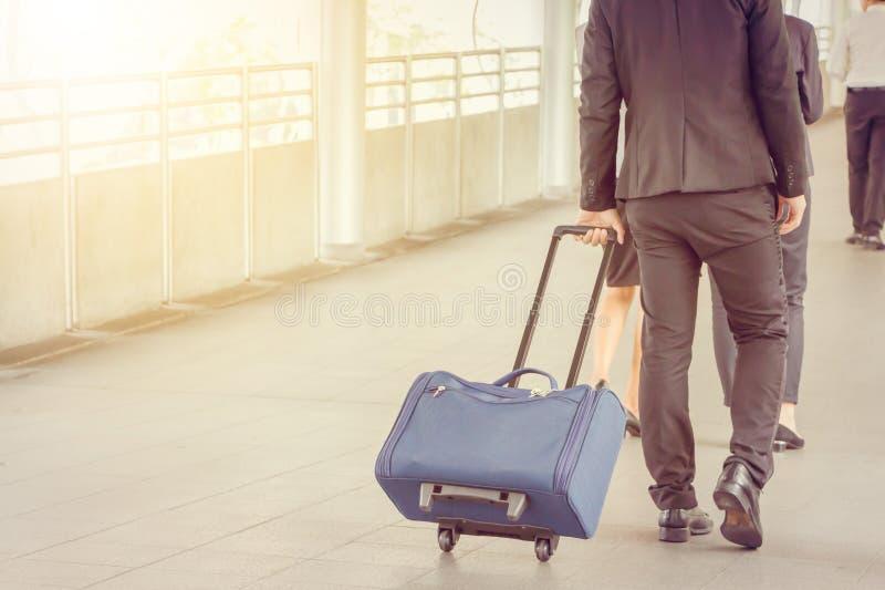 Affärsman- och affärskvinnahandelsresande med bagage på stadsbakgrund, pendlare för affärsfolk som går staden arkivbild