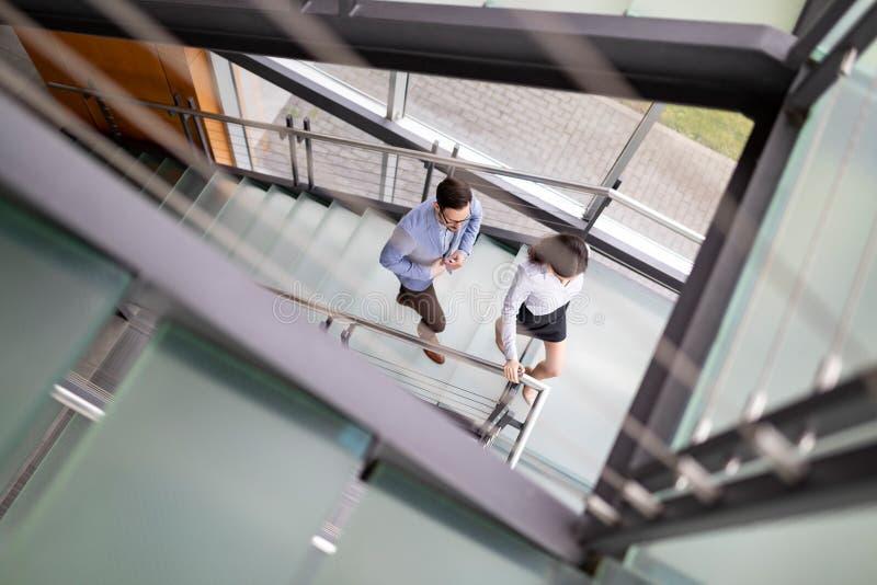 Affärsman- och affärskvinnan går upp trappan fotografering för bildbyråer