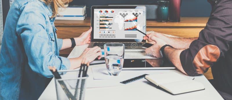 Affärsman- och affärskvinnasammanträde på tabellen framme av bärbara datorn och arbete Grafer, diagram och diagram på PCskärmen arkivbild