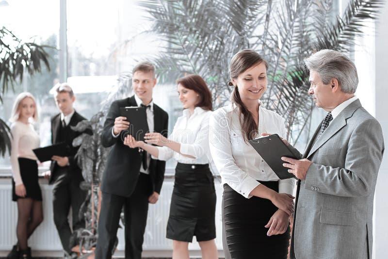 Affärsman och assistent som diskuterar arbetspapper som står i modernt kontor royaltyfri fotografi