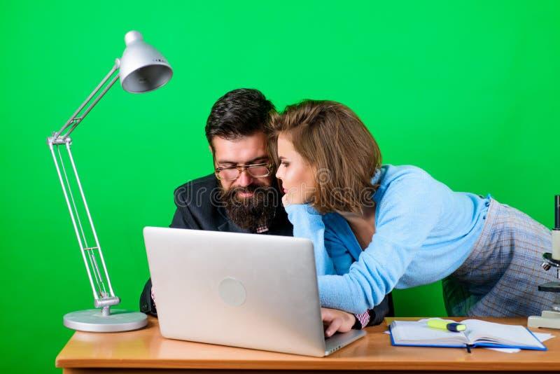 Affärsman- och assistentproblem sekreterare med framstickandet p? arbetsplatsen aff?rspar p? datoren K?rleksaff?r p? arbete fotografering för bildbyråer