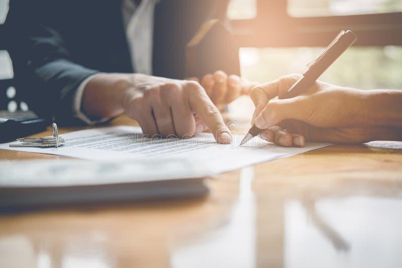 Affärsman och fastighetsmäklare som undertecknar ett dokument för husaffär, arkivbilder
