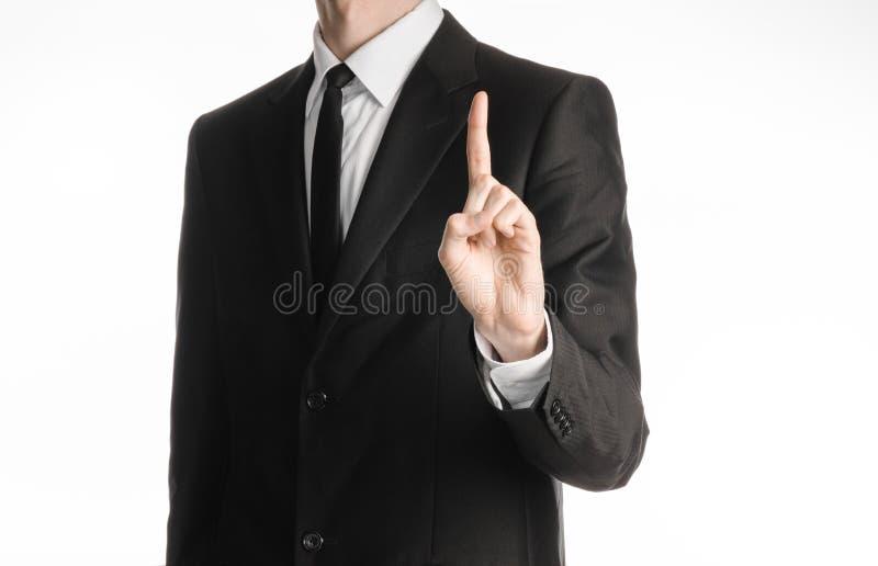 Affärsman och gestämne: en man i en svart dräkt med ett finger för gest för bandvisninghand som isoleras upp på vit bakgrund i st royaltyfri fotografi
