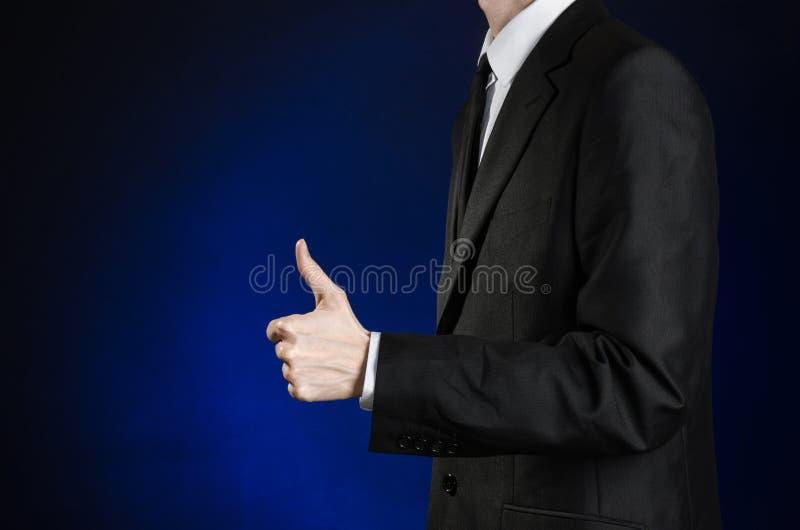 Affärsman och gestämne: en man i en svart dräkt och gester för hand för vitskjortavisning tummar-upp på ett mörker - blå bakgrund royaltyfria foton