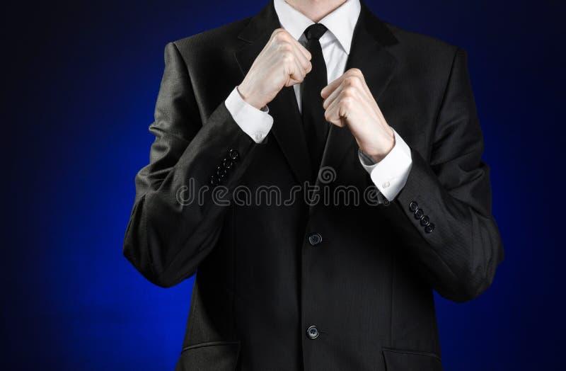 Affärsman och gestämne: en man i en svart dräkt- och vitskjorta som rymmer hans nävar främsta av honom på ett mörker - blå bakgru royaltyfria bilder