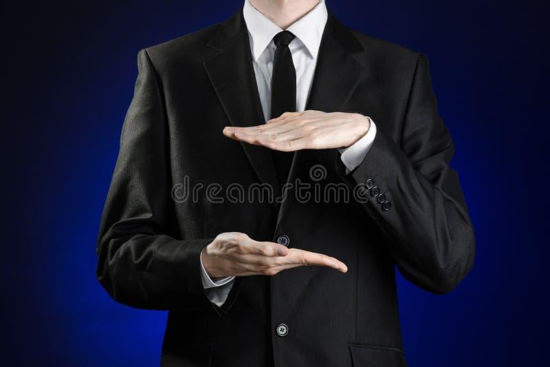 Affärsman och gestämne: en man i en svart dräkt- och vitskjortavisning gör en gest med händer på ett mörker - blå bakgrund i dubb royaltyfri bild