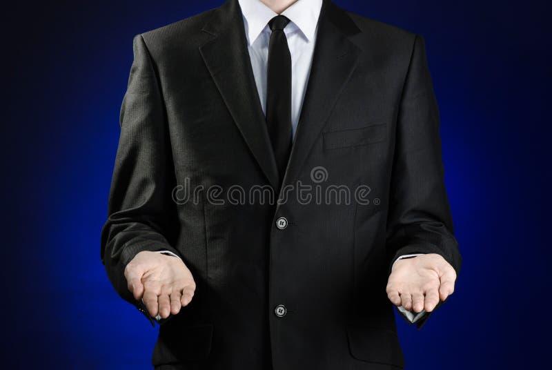 Affärsman och gestämne: en man i en svart dräkt- och vitskjortavisning gör en gest med händer på ett mörker - blå bakgrund i dubb arkivfoton