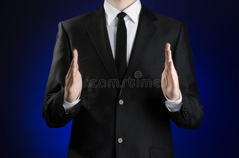 Affärsman och gestämne: en man i en svart dräkt- och vitskjortavisning gör en gest med händer på ett mörker - blå bakgrund i dubb arkivfoto