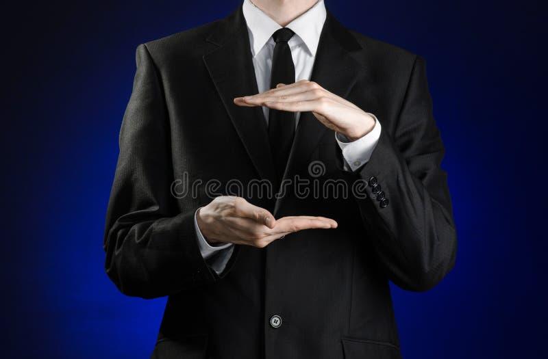 Affärsman och gestämne: en man i en svart dräkt- och vitskjortavisning gör en gest med händer på ett mörker - blå bakgrund i dubb royaltyfria bilder