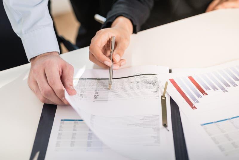 Affärsman och kvinna som analyserar finansiella rapporter royaltyfri bild