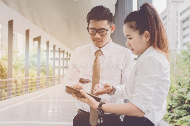 Affärsman och kvinna som använder minnestavlan av att arbeta Möten de kommersiella aktiviteterna, i att främja Skapa tillsammans  royaltyfri bild
