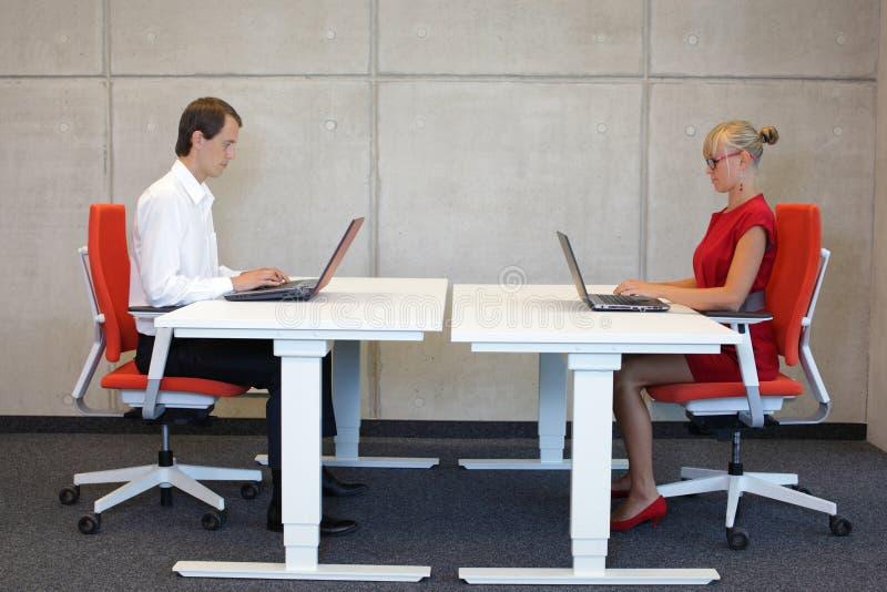 Affärsman och kvinna som arbetar i korrekt sammanträdeställing med bärbara datorer som sitter på stolar royaltyfri bild