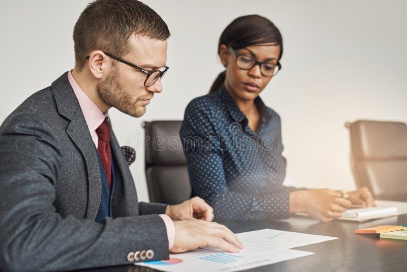 Affärsman och kvinnor som har ett allvarligt möte arkivfoton