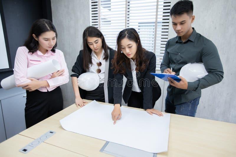 Affärsman- och teknikergrupp som använder anteckningsboken för affärspartners som diskuterar dokument och idéer på möte- och affä arkivfoton
