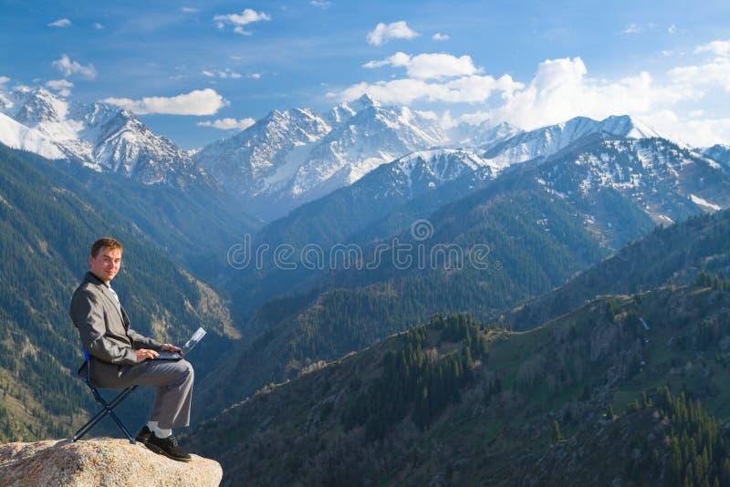 Affärsman på överkanten av berg genom att använda hans bärbar dator royaltyfri fotografi
