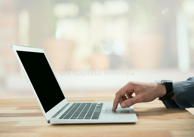 Affärsman på bärbara datorn i ljust nytt rum royaltyfria foton