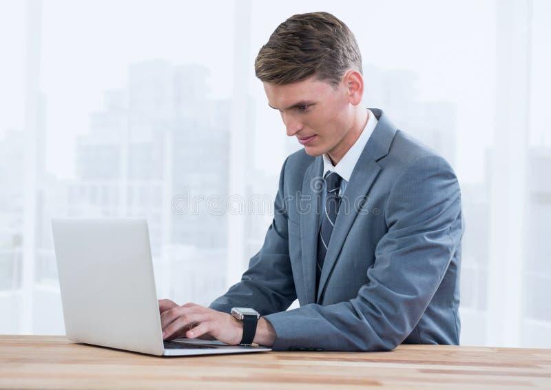 Affärsman på bärbara datorn mot ljusa fönster med staden royaltyfri fotografi