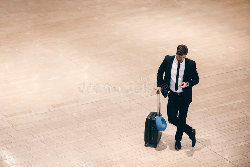 Affärsman på flygplatsterminalen med resväskan och mobiltelefonen royaltyfria bilder