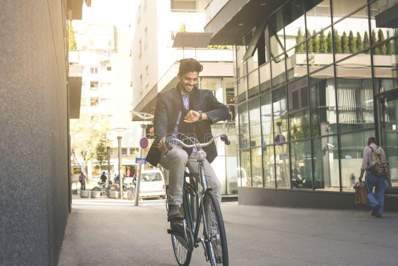 Affärsman på gatan som kör cykeln och kontrollerar på luntan arkivfoto