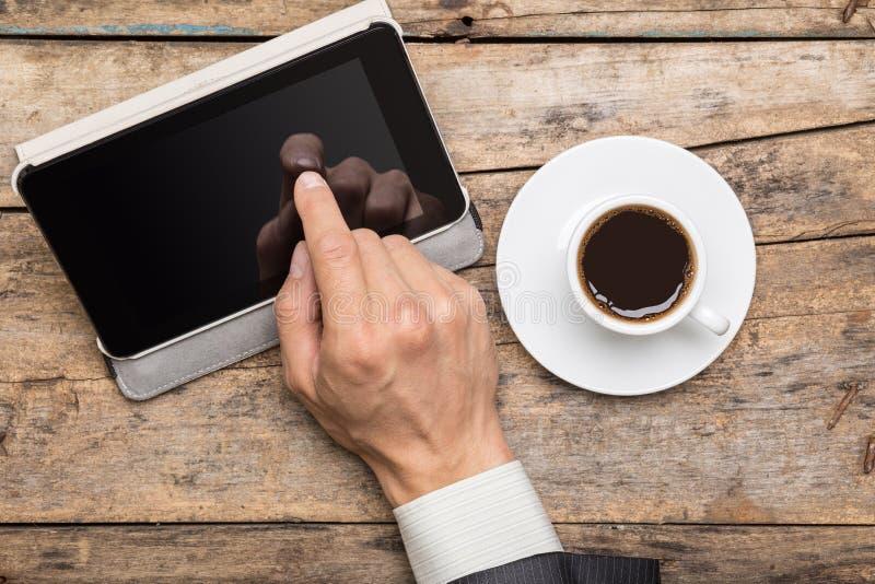 Affärsman på kaffeavbrottet genom att använda minnestavlaPC arkivfoto